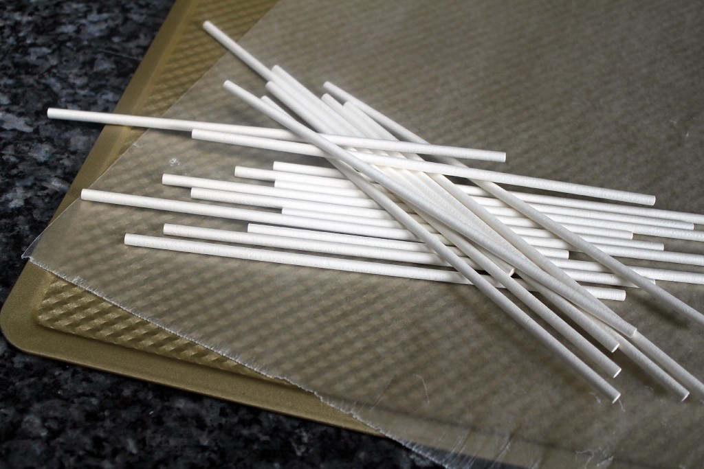 Lollipop sticks, baking sheet lined with parchment paper.