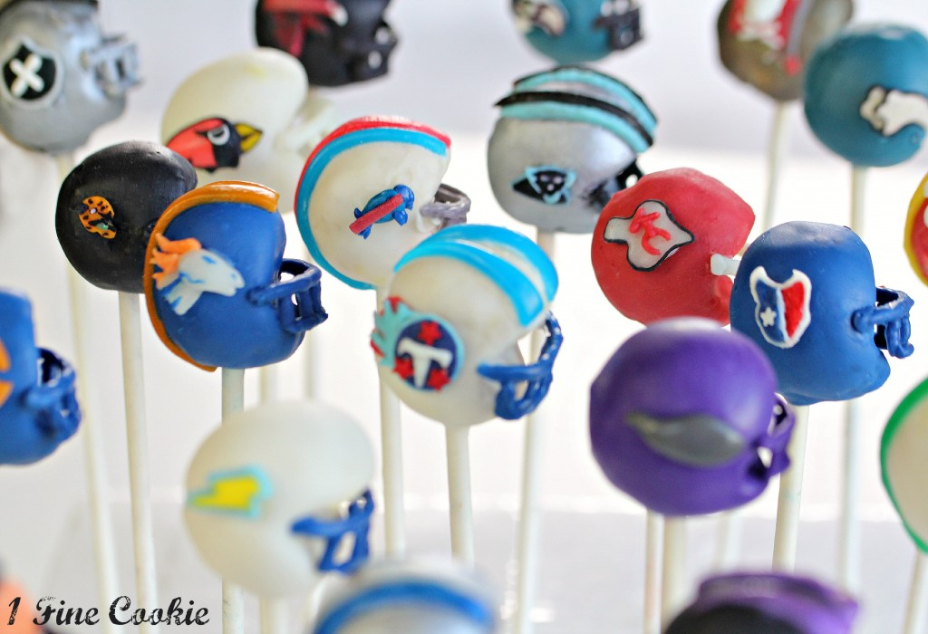 Cut a triangle out of your cake balls, 1 fine cookie, football cake pops, football helmet, football helmet cake pops, football, football cake, football recipes, nfl recipes, football party ideas, football dessert table, nfl dessert table, dessert table, recipes, how to, diy, nfl cake pops, baltimore ravens, baltimore ravens cake pops, ravens cake pops, ravens, 49ers, san fransisco 49ers, san fransisco 49ers cake pops, 49ers cake pops, cake, pops, how to make cake pops, football cake pops, football helmet cake pops, Bears, bears cake pops, chicago bears cake pops, Bengals, bengals cake pops, cincinatti cake pops, cincinatti bengals, cincinatti bengals cake pops, Bills, buffalo bills, bills cake pops, buffalo bills cake pops, Broncos, broncos cake pops, denver broncos cake pops, denver cake pops, denver, Browns, browns cake pops, cleveland, cleveland browns, cleveland cake pops, bfl cake pops, cleveland browns cake pops, Bucaneers, bucaneers cake pops, tampa bay bucaneers, tampa bay bucaneers cake pops, tampa bay cake pops, Cardinals, cardinals cake pops, arizona cardinals, arizona cardinals cake pops, arizona cake pops, Chargers, chargers cake pops, san diego chargers, san diego chargers cake pops, Cheifs, chiefs cake pops, kansas city chiefs cake pops, kansas city cake pops, kansas city cake pops, Colts, Indianapolis colts, colts cake pops, indianapolis colts cake pops, indianapolis cake pops, Cowboys, cowboys cake pops, dallas cake pops, dallas, dallas cowboys cake pops, Dolphins, miami dolphins, dolphins cake pops, miami dolphins cake pops, miami cake pops, Philadelphia cake pops, philadelphia eagles cake pops, Eagles cake pops, Falcons, falcons cake pops, atlanta cake pops, atlanta falcons, atlanta falcons cake pops, Giants, giants cake pops, ny cake pops, ny giants, ny giants cake pops, Jaguars cake pops, jaguars, jacksonville jaguars, jacksonville jaguars cake pops, jaguars cake pops, Jets, ny jets, jets cake pops, ny jets cake pops, Lions, lions cake pops, detroit cake pops, detroit lions, detroit lions cake pops, sport cake pops, lions cake pops, Packers, green bay packers, green bay cake pops, green bay, packers cake pops, green bay packers cake pops, Panthers, carolina, carolina panthers, panthers cake pops, carolina cake pops, carolina panthers cake pops, Patriots, new england, new england patriots, patriots cake pops, new england cake pops, new england patriots cake pops, Raiders, oakland, oakland raiders, oakland raiders cake pops, raiders cake pops, oakland cake pops, Rams, rams cake pops, st. louis rams, st. louis, st. louis cake pops, rams cake pops, st. louis rams cake pops, Ravens, baltimore ravens, baltimore ravens cake pops, ravens cake pops, baltimore cake pops, Redskins, washington, washington redskins, washington redskins cake pops, washington cake pops, redskins cake pops, washington cake pops, Saints, New orleans, new orleans saints, new orleans saints cake pops, new orleans cake pops, saints cake pops, Seahawks, seahwaks cake pops, seattle cake pops, seattle seahawks, seattle seahawks cake pops, Steelers, pittsburgh steelers, pittsburgh, steelers cake pops, pittsburgh steelers cake pops, pittsburgh cake pops, texans cake pops, texan cake pops, houston texans, houston cake pops, houston Texans cake pops, texans cake pops, Titans, tennessee titans, Tennessee, titans cake pops, Tennessee cake pops, Tennessee cake pops, Vikings, vikings cake pops, Minnesota cake pops, minnesota vikings cake pops, minnesota, minnesota vikings, football helmet dessert,