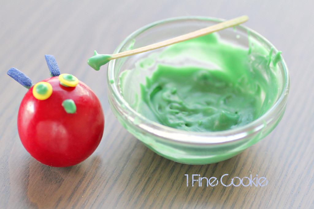 How to Make Hungry Caterpillar Cakes and Cupcakes by 1 Fine Cookie, Hungry, Caterpillar, cake, topper, cupcake, piping, frosting, swirl, corkscrew, gum ball, decoration, how, to, idea, children, child's, kids, birthday, party, sprinkles, tootsie rolls, fondant, candy, green, red, book, literature, kindergarten, reading, theme, school, class, teachers, legs, antlers, easy,